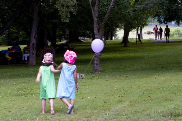 Children with hats walking with balloons.