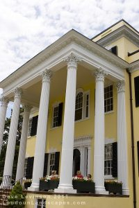 Tall yellow plantation mansion with several white columns.